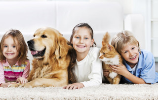 three children laying next to a dog and cat on a beige carpet