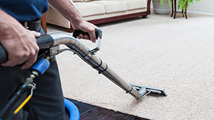 Professional steam cleaning of a beige nylon carpet in a residential home.