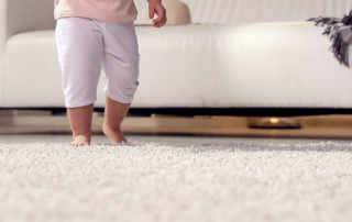 baby walking across white soft carpet at home