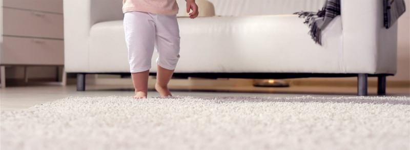 baby walking across white soft carpet at home