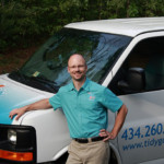 Tidy Guy standing by his work van on a sunny day, wearing a uniform and smiling