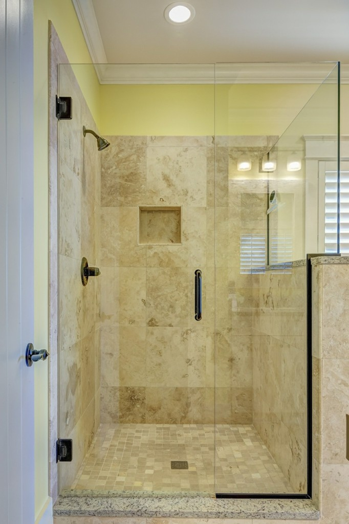 Beautifully restored shower glass door and side panel in the bathroom.