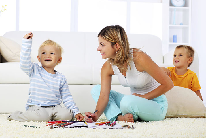 mother and her children playing together on a soft carpet
